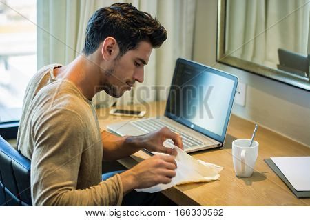 Waist Up Profile of Young Attractive Man with Dark Hair, Sitting at Computer Desk Working on Homework or on His Start-up Business, in Dorm Room