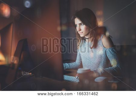 Attractive young woman working on coworking office at night. Girl using contemporary desktop computer, blurred background. Horizontal, film effect, reflections