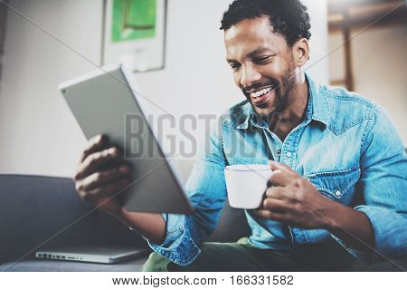 Young bearded African man using tablet while sitting on sofa and holding white cup coffee in hand at home.Concept people working with mobile gadget.Blurred background