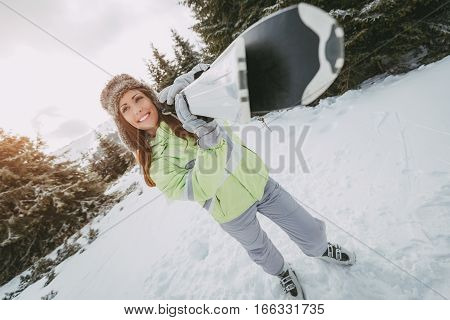 Beautiful young woman enjoying in ski vacations. She standing with skis and looking away with smile.