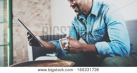 Smiling bearded African man using tablet while sitting on sofa and holding white cup coffee in hand at home.Concept people working with mobile gadget.Blurred background