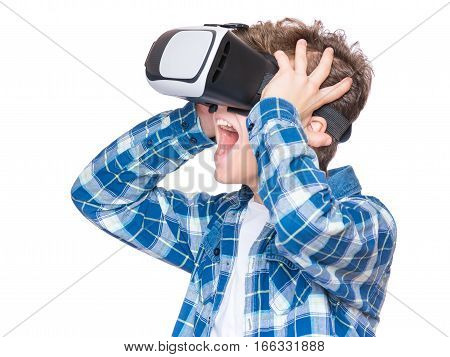 Amazed teen boy wearing virtual reality goggles watching movies or playing video games, on white. Surprised teenager looking in VR glasses. Emotional portrait of child experiencing 3D gadget technology.