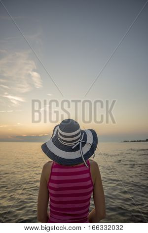 Rear view of woman in pink sleeveless shirt and broad-brim watching sunset over sea copy space.