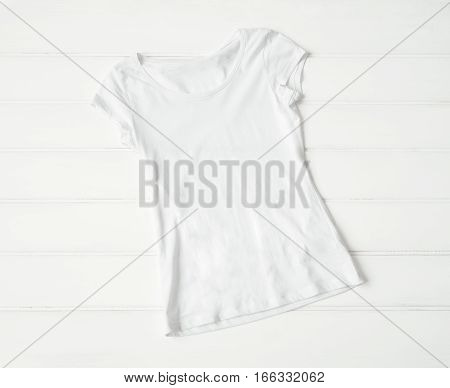 White women's t-shirt laid out on the floor
