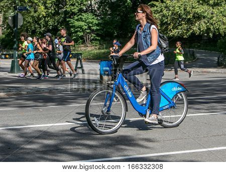 New York September 17 2016: A young woman is riding a citibike in Central Park.