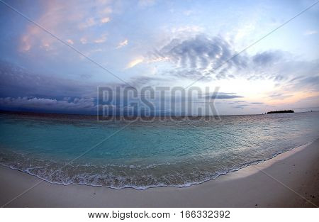 A view of the sky and Indian Ocean from an island in Maldives through a fisheye lens.