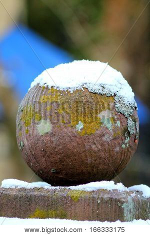 Spherical stone mossy ball with snow hood, fragment of an old  stony fence. Shallow focus background.