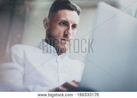 Attractice bearded businessman working in modern office.Man using contemporary notebook.Blurred background. Horizontal, film effect