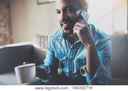 Smiling bearded African man making call by smartphone while sitting on sofa and holding white cup coffee in hand.Concept people working with mobile gadget.Blurred background