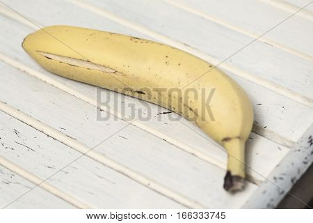 Banana on a striped vintage surface. Food art