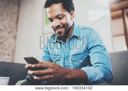 Closeup of smiling bearded African man making text message on smartphone while sitting sofa at modern home.Concept people using mobile devices.Blurred wall background