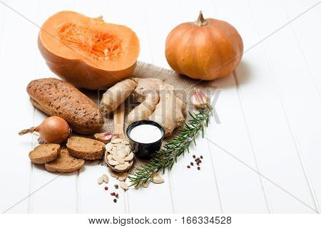 Pumpkin and ingredients for cooking over the white wooden background. Vegetarian food health or cooking concept.