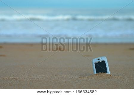 Obsolete technology - old phone buried in sand at beach