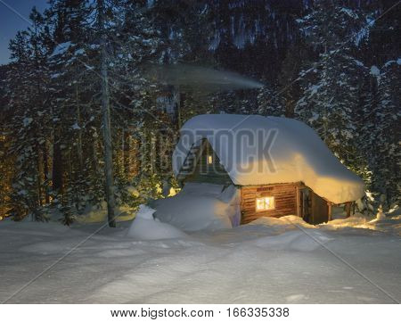 Siberia taiga. Winter dark night and the light from windows of a wooden hut.