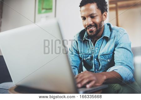 Smiling bearded African man spending free time in sofa and using laptop at modern home.Concept of young people enjoying mobile devices.Blurred background