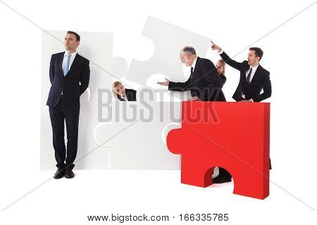 Lazy businessman doesn't want to work with team assembling puzzle