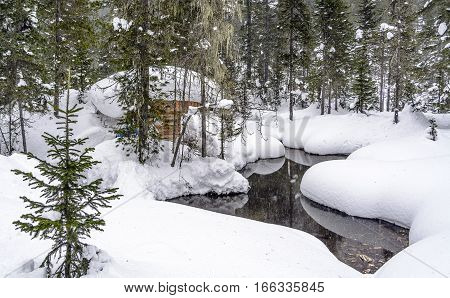 Winter forest, huge snodrifts around. Small hut near stream and silents.