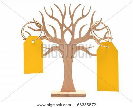 yellow empty paper shopping tag or blank cardboard label for price sell sale or holiday card hang on wooden decorative tree isolated on white background copy space