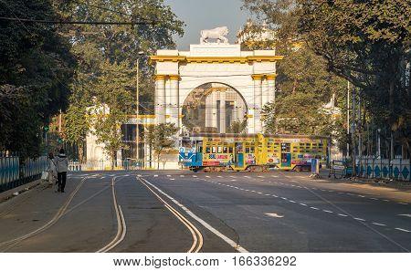 KOLKATA, INDIA -JANUARY 22, 2017: Heritage Kolkata tram passing the front entrance of the historic and Gothic architectural Governor house near Dharamtala Chowringhee area, Kolkata.