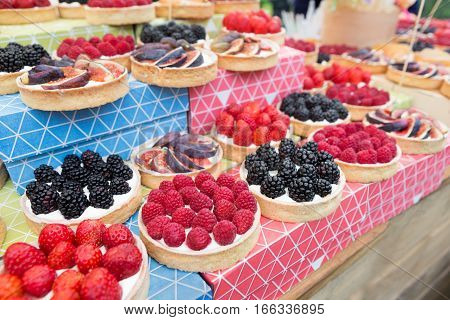 Fruit and berry tarts dessert tray assorted outdoors. Closeup of beautiful delicious pastry sweets with fresh natural blueberries, raspberries and figs. French Bakery catering.