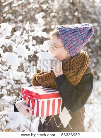 small boy or cute nerd kid in glasses hat sweater and fashionable knitted scarf holds red christmas or new year gift box and cup in sunny winter outdoor on natural background
