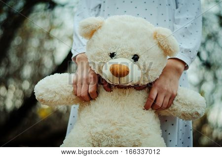 Soft toy bear on hands of girl on sleepwear outdoor.