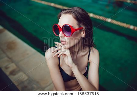 Sexy brunette woman in funny sunglasses with a beautiful professional make up sitting near the pool.