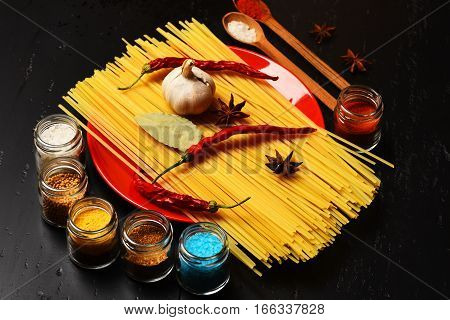 italian pasta with spice in jar chili pepper badian bay leaf and garlic on black background as cooking products with wooden spoon