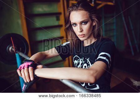 Beautyful sport girl with make up resting on training in the old style gym.