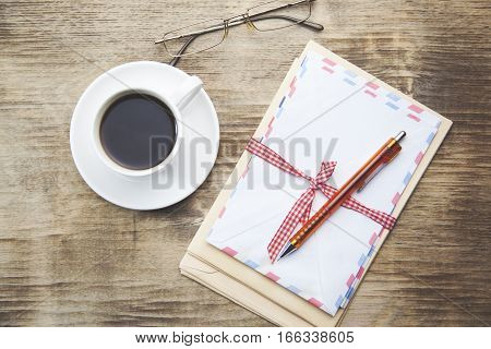 coffee lettersglasses and pen on wooden table