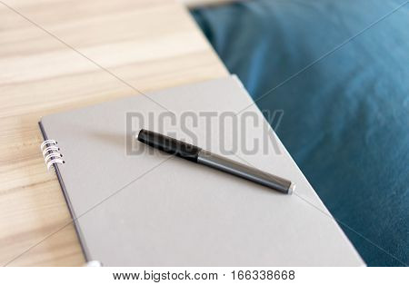 Note with pen beside the pillow on bed. working everywhere