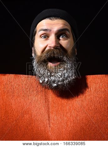handsome bearded man or guy in winter hat with fashionable mustache on happy face and snow in beard near red paper on black background copy space
