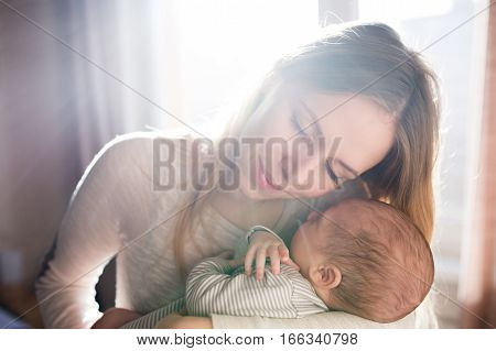 Beautiful young mother holding her sleeping baby son in her arms, eyes closed