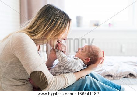 Beautiful young mother with her newborn baby son, sitting on bed in her bedroom, caressing him