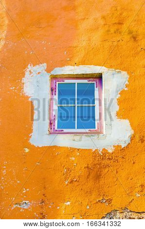 Vintage wooden window with blue glass on yellow cement crack wall can be used for background