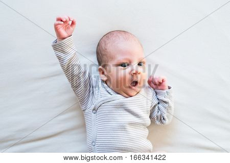 Cute newborn baby boy in striped onesie lying on bed, arm raised, superhero pose, mouth open.