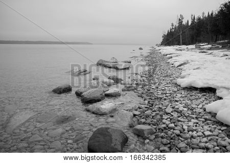 A geometric looking bw image of conifers snow rocks and clear lake water and an island on the horizon.