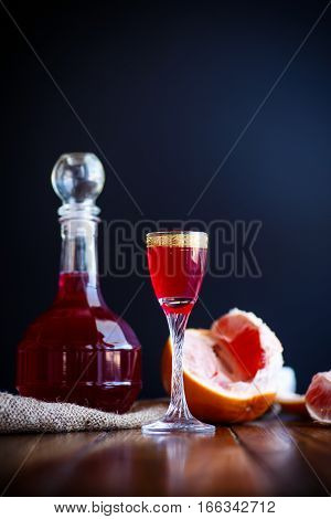 sweet grapefruit alcoholic cordial in the decanter with a glass on a dark table