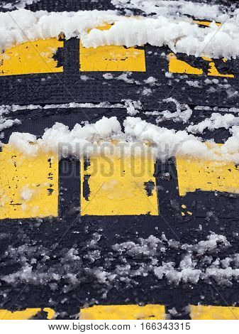 Plastic speed bump obstacle covered with snow.