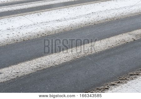 Road is getting covered with fresh snow.