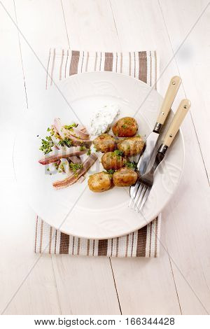 fine dinning with herring stripes and cooked baby potatos on a plate