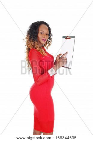 A beautiful African American woman in a tight red dress showing on a clipboard standing in profile isolate for white background.
