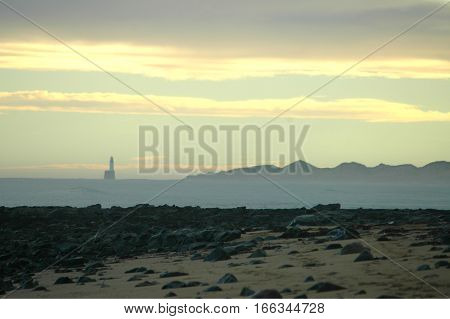 Silhouetted lighthouse and sand dunes at dusk, Scotland. Rattray Head.
