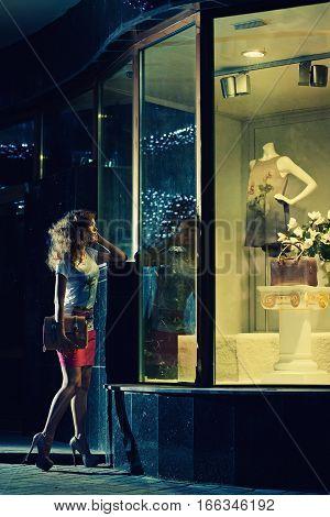 fashion woman posing near mannequin. Shopping in fashion boutique.