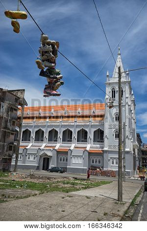 June 9 2016 Colon Panama: shoes tossed on electrical wire with newly renovated cathedral in the background in the port town