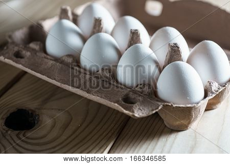 White eggs in opened box on wooden background