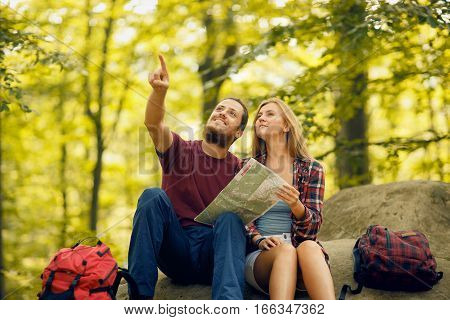 Blond girl in checkered shirt and bearded man with backpacks seating on the rock in the forest