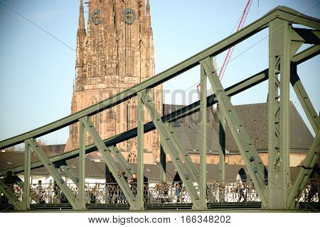 FRANKFURT, GERMANY - JANUARY 05: Visitors crossing the bridge Iron Bridge in the old town of Frankfurt with the imperial cathedral of St. Bartholomew in the background on January 05, 2017 in Frankfurt.