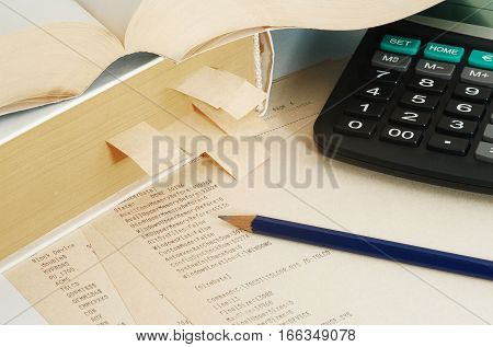 Thick reference book with bookmarks papers with programm listing calculator and pencil