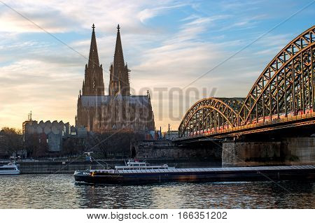Cologne Cathedral and Hohenzollern Bridge in the rays of the evening sun. Under the bridge of the ship sails. The Cathedral, built in Gothic style in honor of St. Peter the Apostle and the Virgin Mary.